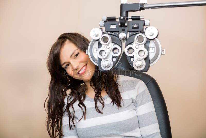 Donna felice che si siede dietro Phoropter immagine stock libera da diritti
