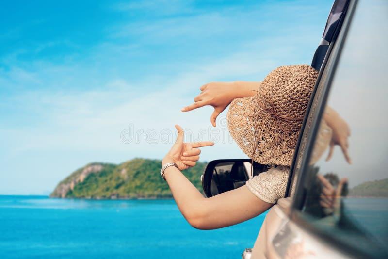 Donna felice che si siede nell'automobile e nella stagione estiva di viaggio sul mare fotografie stock