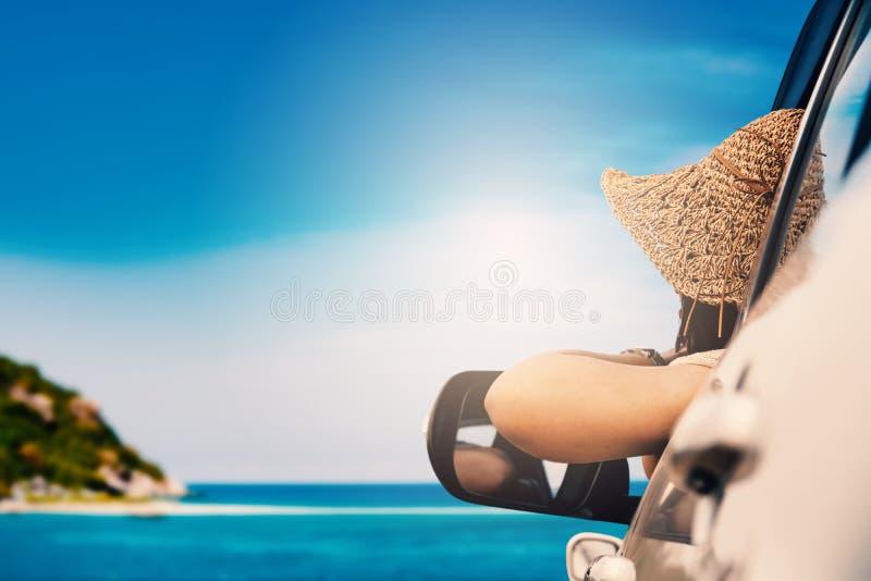 Donna felice che si siede nell'automobile e nella stagione estiva di viaggio sul mare immagine stock libera da diritti