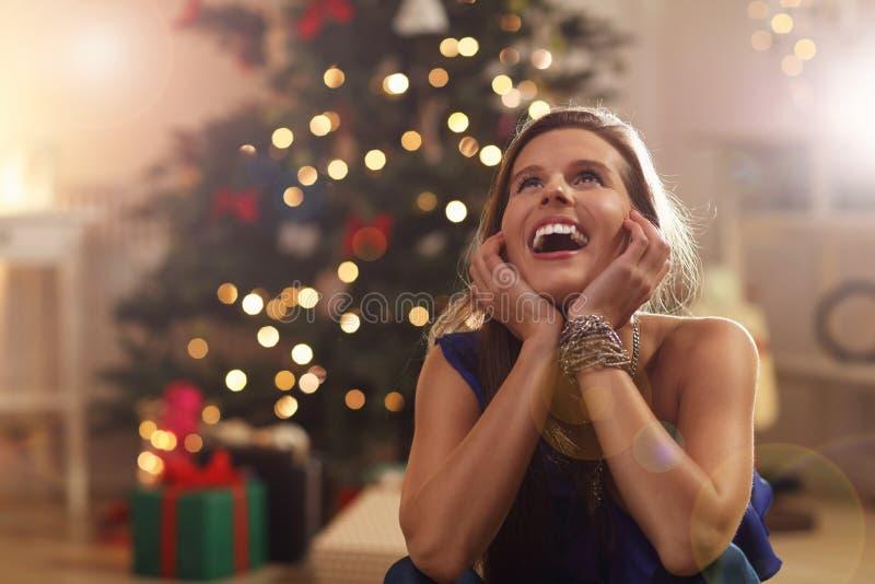 Donna felice che si siede sopra l'albero di Natale immagini stock