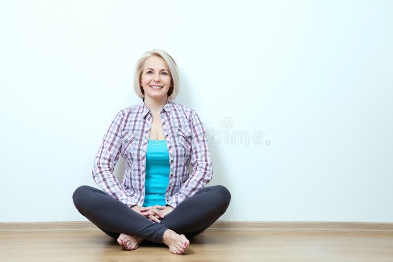 Donna felice che si siede sul pavimento con le gambe attraversate in studio fotografia stock