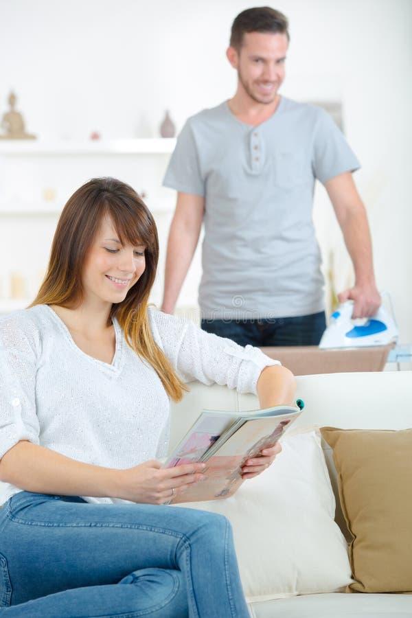 Donna felice che si siede sulla rivista della lettura dello strato immagini stock libere da diritti
