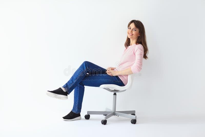 Donna felice che si siede sulla sedia su fondo bianco immagini stock libere da diritti