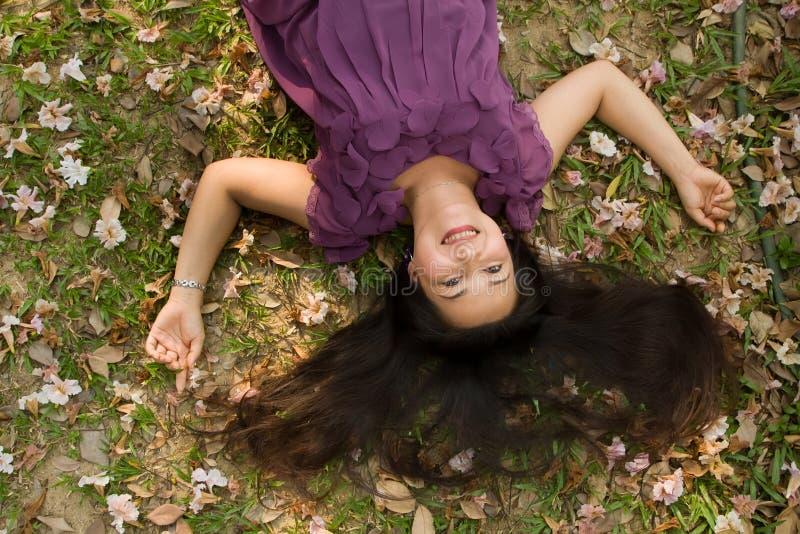 Donna felice che si trova sull'erba fotografia stock