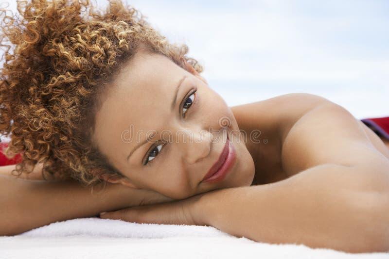 Donna felice che si trova sulla Tabella di massaggio immagini stock