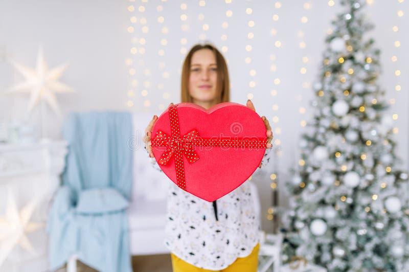 Donna felice che tiene un contenitore rosso di regalo nella decorazione di natale a casa immagine stock libera da diritti