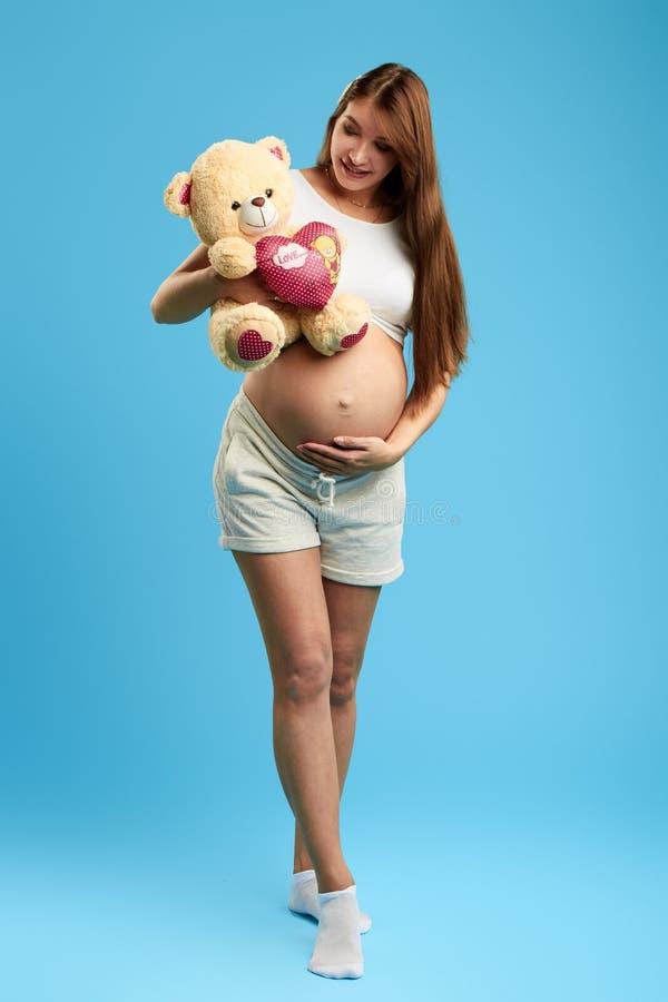 Donna felice che tocca la sua pancia mentre preoccupandosi l'orso fotografia stock