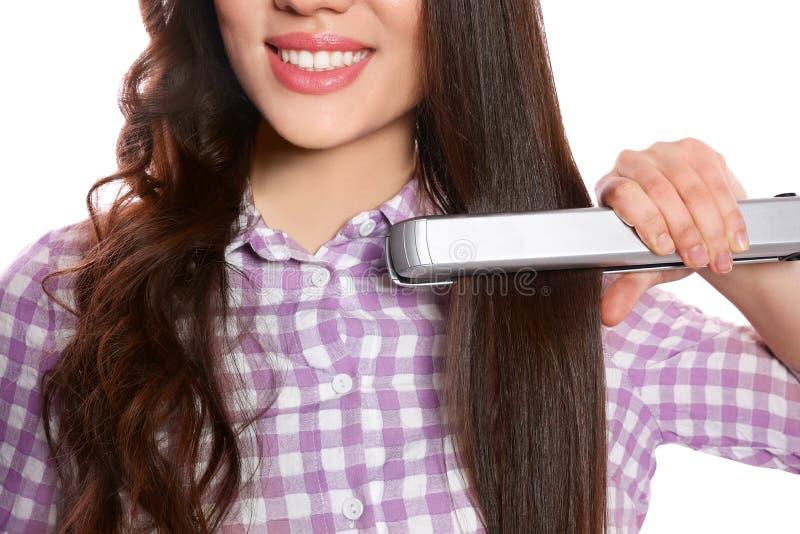 Donna felice che usando il ferro dei capelli su fondo bianco fotografie stock