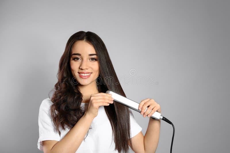 Donna felice che usando il ferro dei capelli su fondo grigio fotografia stock