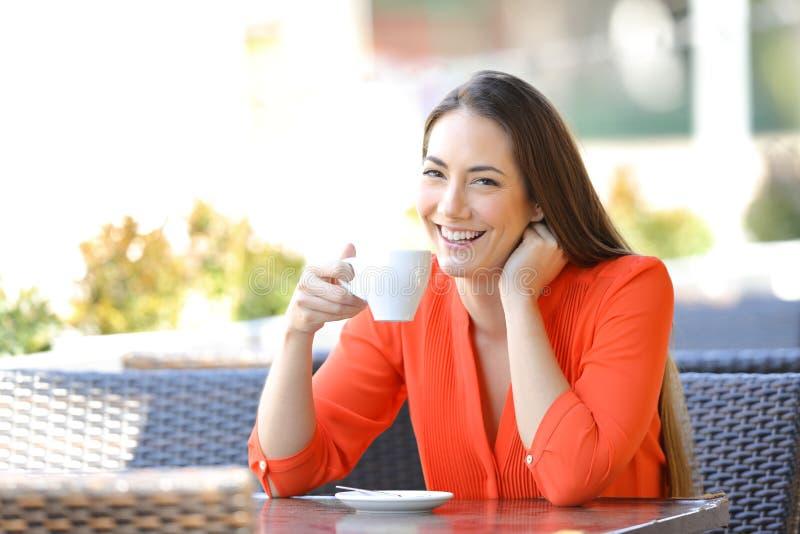 Donna felice che vi esamina che tenete tazza da caffè in una barra fotografie stock libere da diritti