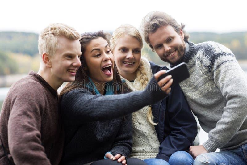 Donna felice con gli amici che prendono autoritratto al campeggio fotografie stock