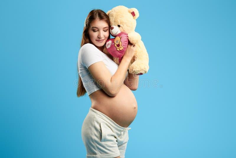 Donna felice con gli occhi chiusi che gode del gioco con il suo bambino nell'utero immagine stock libera da diritti