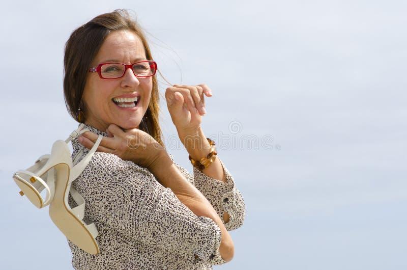 Donna felice con i pattini dello stiletto sopra la spalla fotografia stock libera da diritti