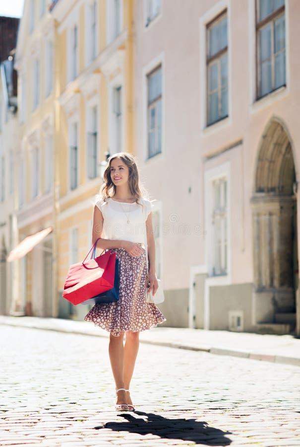 Donna felice con i sacchetti della spesa che cammina nella città immagine stock libera da diritti
