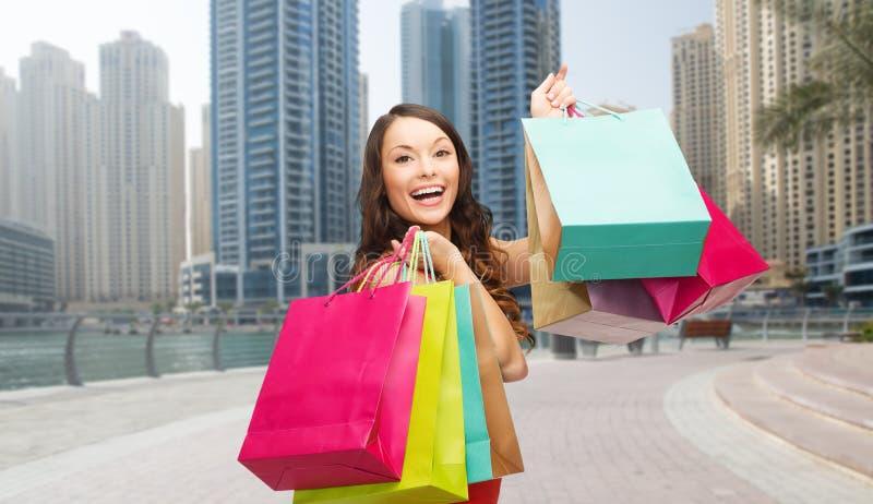 Donna felice con i sacchetti della spesa sopra la città della Dubai fotografia stock