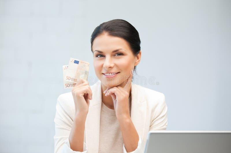 Donna felice con il computer portatile ed i soldi fotografie stock