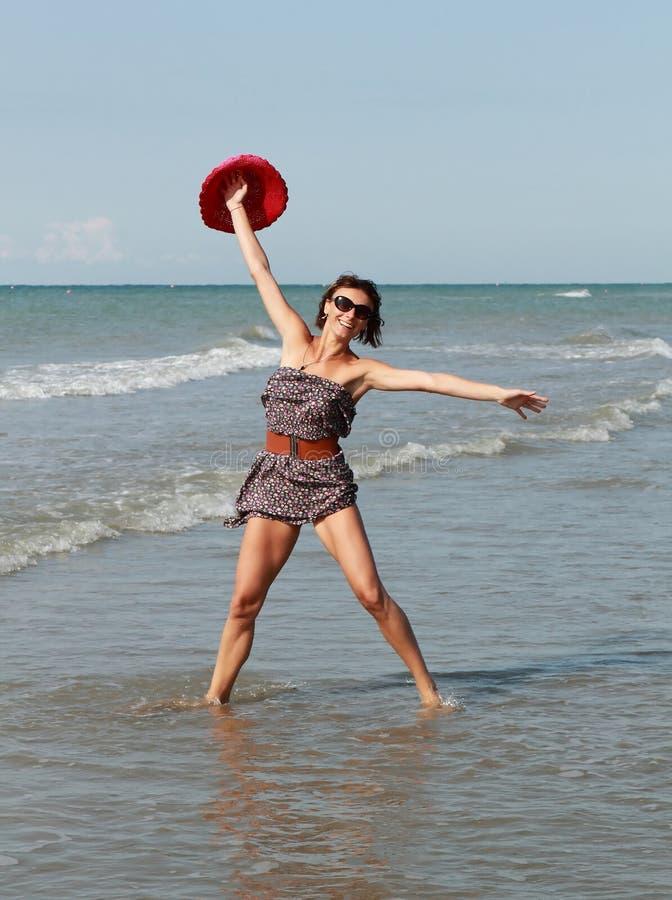 Donna felice con il dancing del cappello in mare fotografie stock libere da diritti