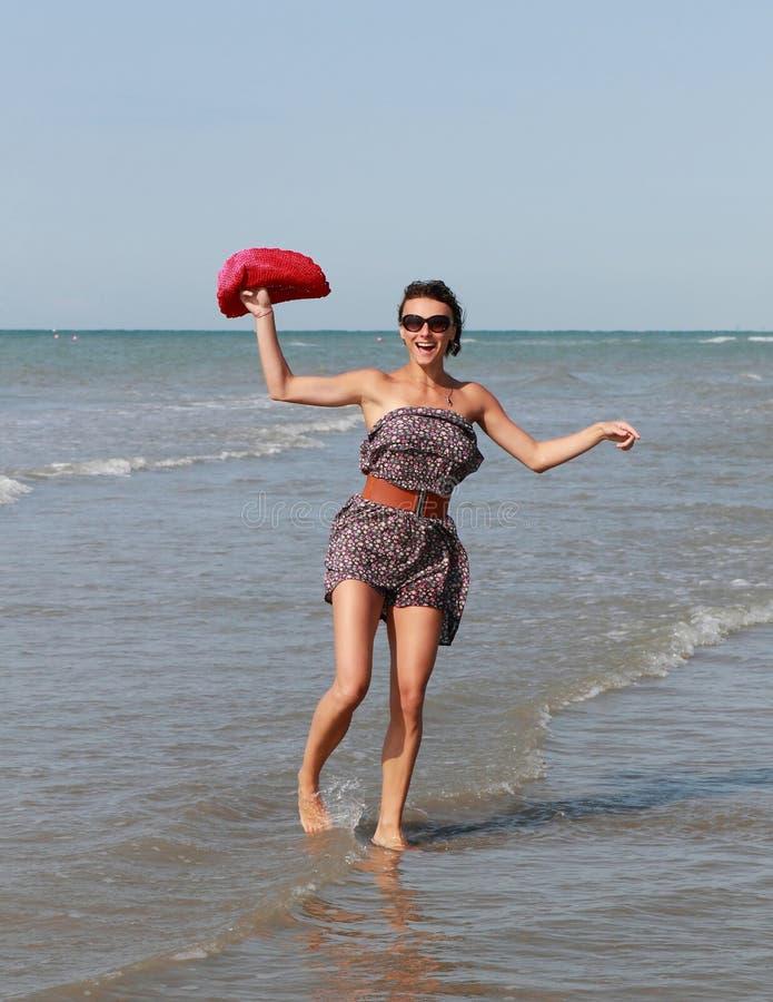 Donna felice con il dancing del cappello in mare immagine stock libera da diritti