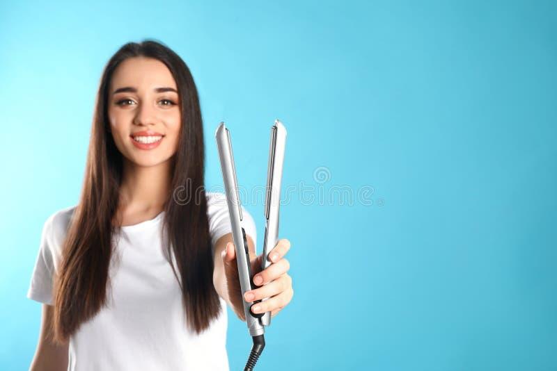 Donna felice con il ferro dei capelli sul fondo di colore fotografia stock libera da diritti