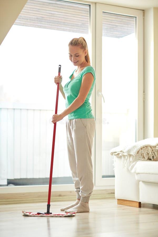 Donna felice con il pavimento di pulizia di zazzera a casa immagine stock