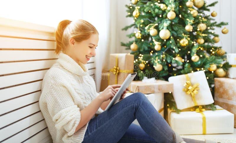 Donna felice con il pc della compressa alla mattina vicino all'albero di Natale immagine stock libera da diritti