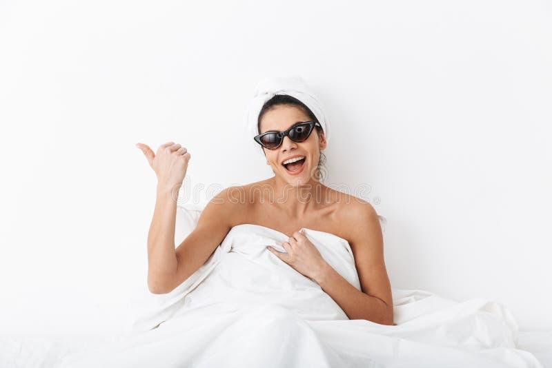 Donna felice con l'asciugamano sulle bugie cape a letto sotto la coperta isolata sopra indicare d'uso degli occhiali da sole del  immagine stock