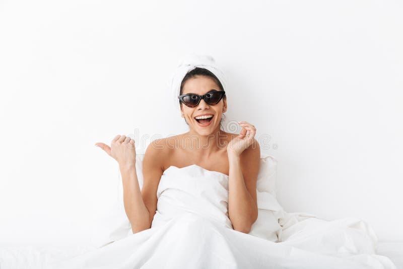 Donna felice con l'asciugamano sulle bugie cape a letto sotto la coperta isolata sopra indicare d'uso degli occhiali da sole del  fotografie stock