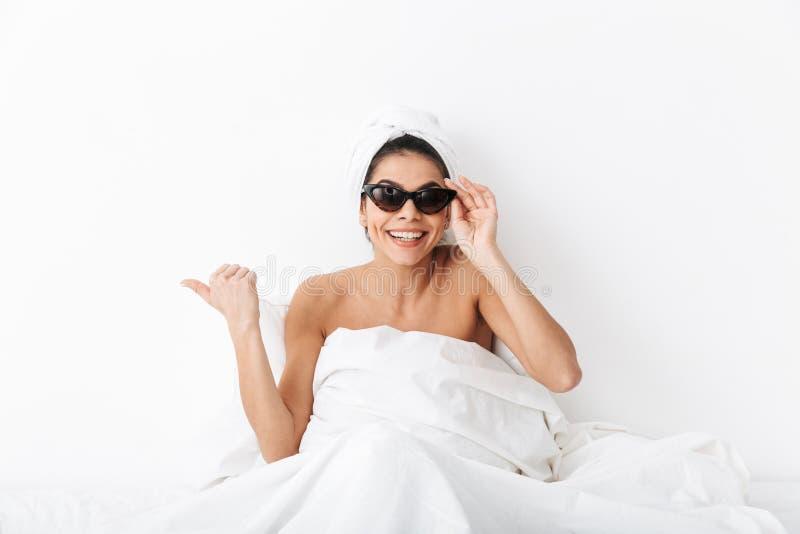 Donna felice con l'asciugamano sulle bugie cape a letto sotto la coperta isolata sopra indicare d'uso degli occhiali da sole del  immagine stock libera da diritti
