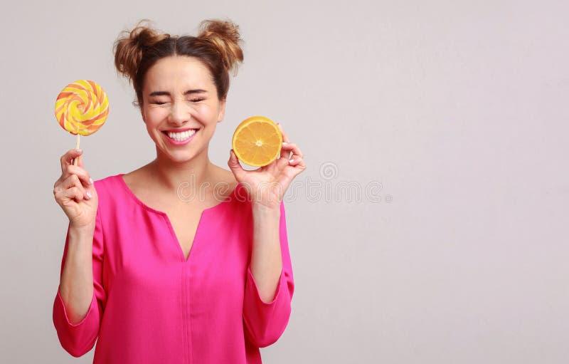 Donna felice con la lecca-lecca e l'arancia sopra fondo fotografia stock