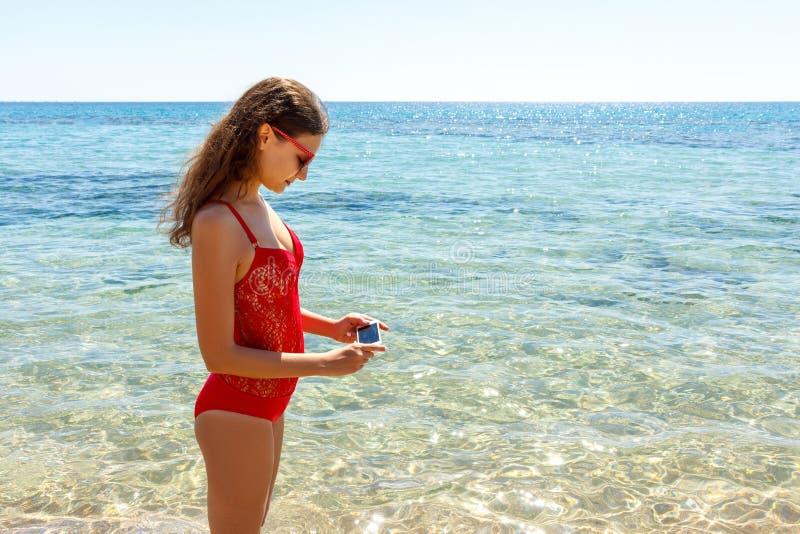 Donna felice con una fotografia del mare Una ragazza sta facendo una foto con un chiaro mare fotografia stock libera da diritti