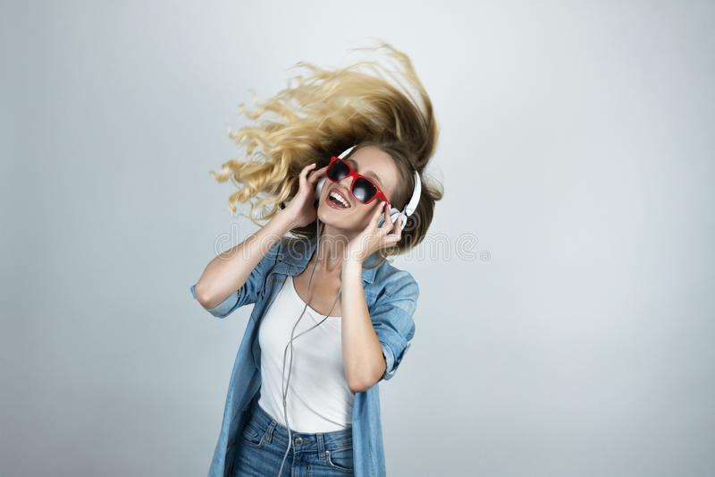 Donna felice in cuffie ed occhiali da sole che ascolta il fondo isolato bianco ballante di musica nel moto fotografie stock