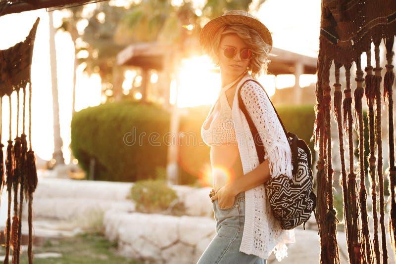 Donna felice dei pantaloni a vita bassa divertendosi sulla vacanza in cappello ed occhiali da sole Ragazza soleggiata di modo di  fotografia stock
