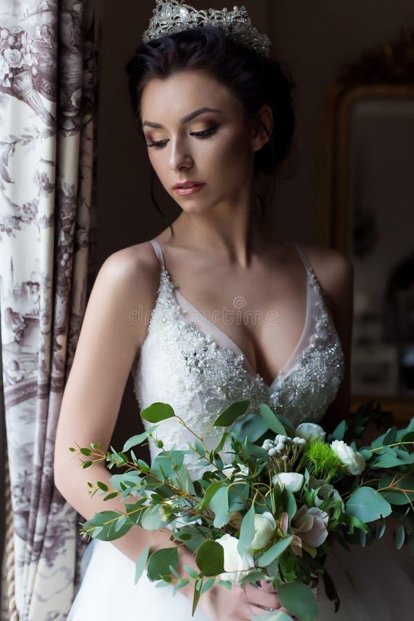 Donna felice della bella sposa sexy delicata con una corona sulla sua testa dalla finestra con un grande mazzo di nozze in un bia immagini stock libere da diritti