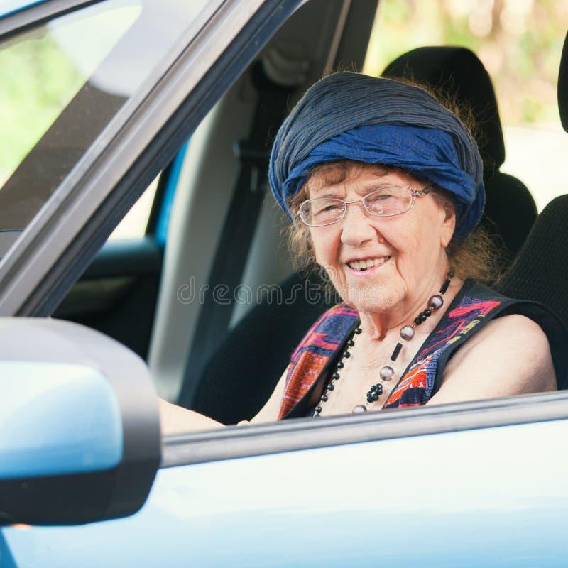 Donna felice della nonna all'automobile immagine stock libera da diritti