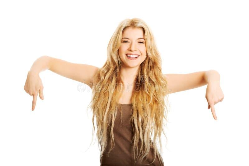 Donna felice dello studente che indica giù fotografie stock libere da diritti
