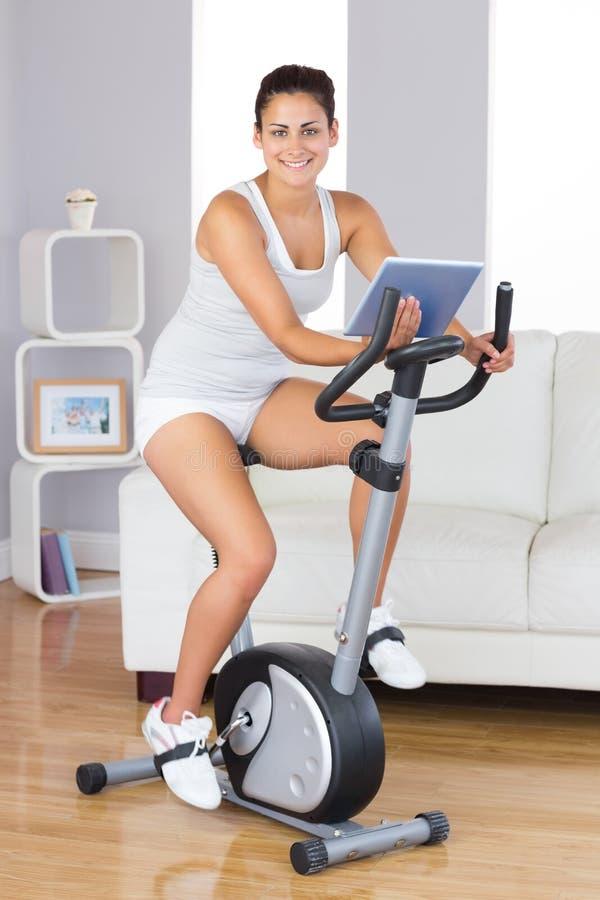Donna felice di addestramento che per mezzo di una bici di esercizio mentre tenendo una compressa fotografie stock libere da diritti