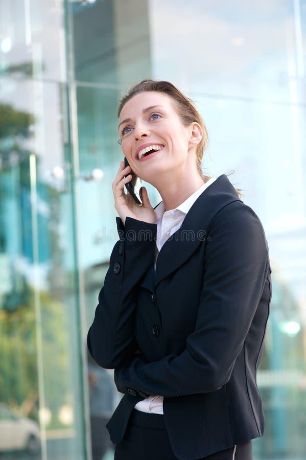 Donna felice di affari che cammina e che parla sul cellulare fotografia stock libera da diritti
