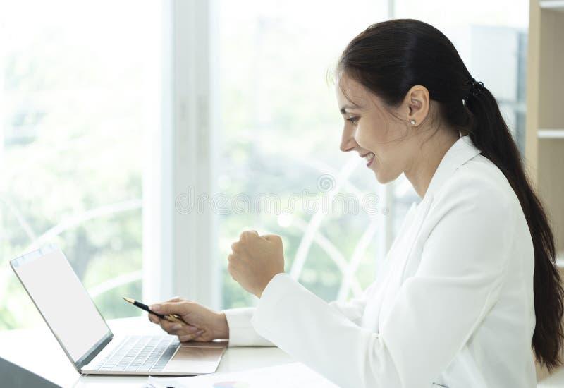 Donna felice di affari che guarda computer con le armi su riuscito immagini stock libere da diritti