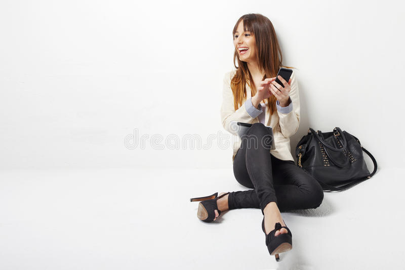 Donna felice di affari che per mezzo di un telefono astuto immagini stock