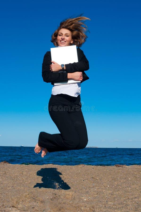 Donna felice di affari che salta con il computer portatile immagine stock