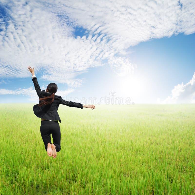 Donna felice di affari che salta in giacimento e cielo blu verdi del riso fotografia stock