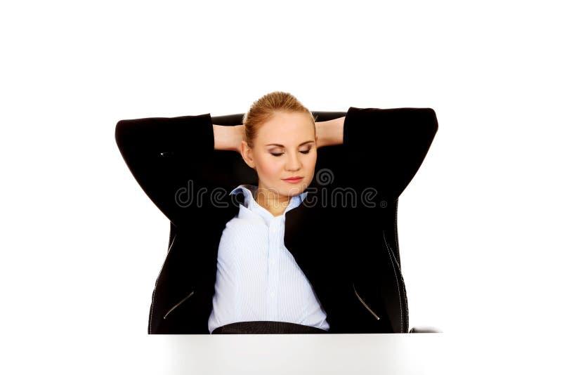 Donna felice di affari che si rilassa nell'ufficio fotografia stock