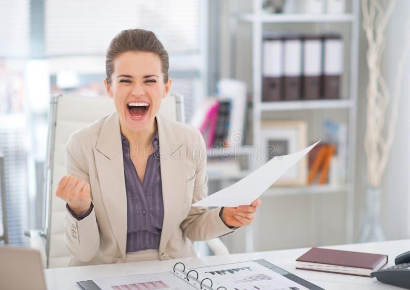 Donna felice di affari con l'esultanza del documento fotografie stock