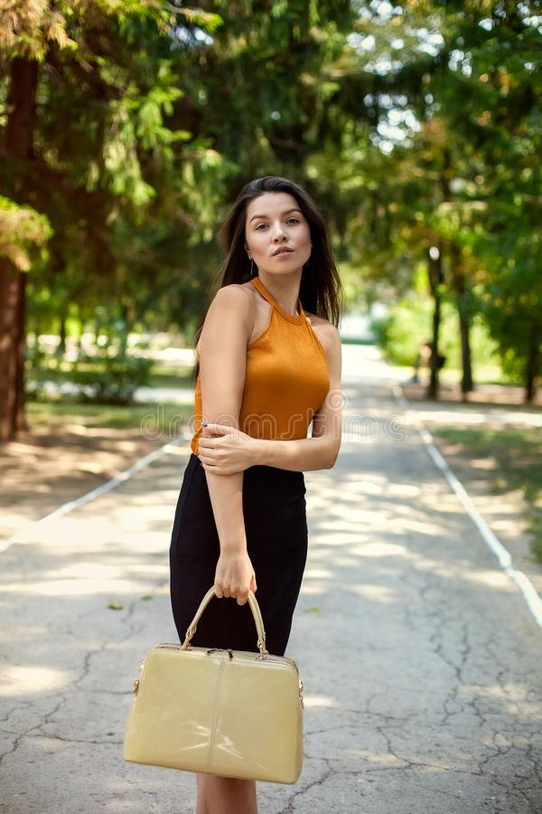 Donna felice di affari con la borsa a disposizione in parco all'aperto fotografie stock