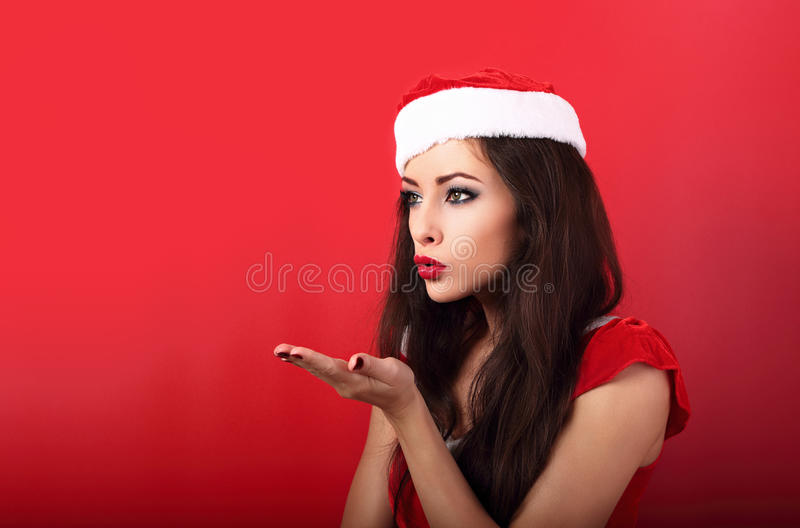 Donna felice di bello trucco in costume del Babbo Natale che soffia sulla s immagini stock libere da diritti