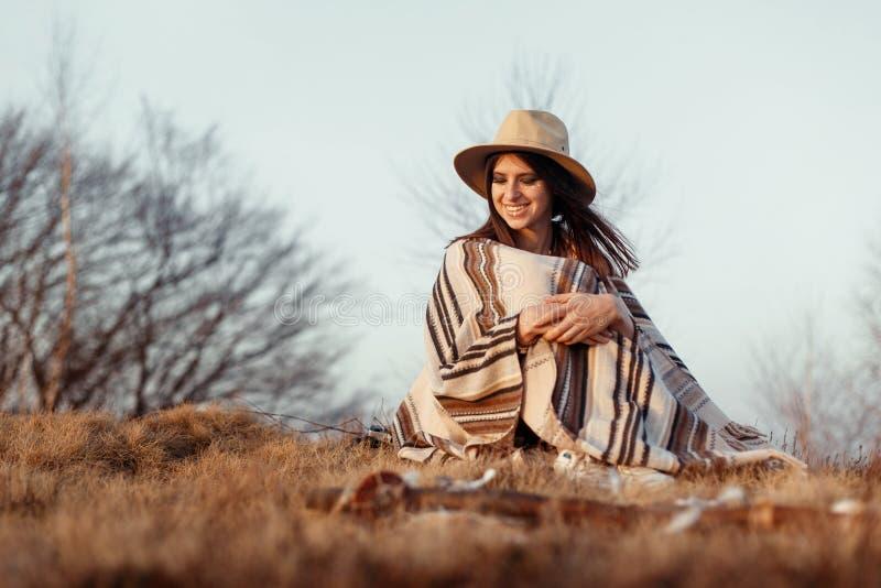 Donna felice di boho che si siede al tramonto in montagne, cappello d'uso e fotografie stock