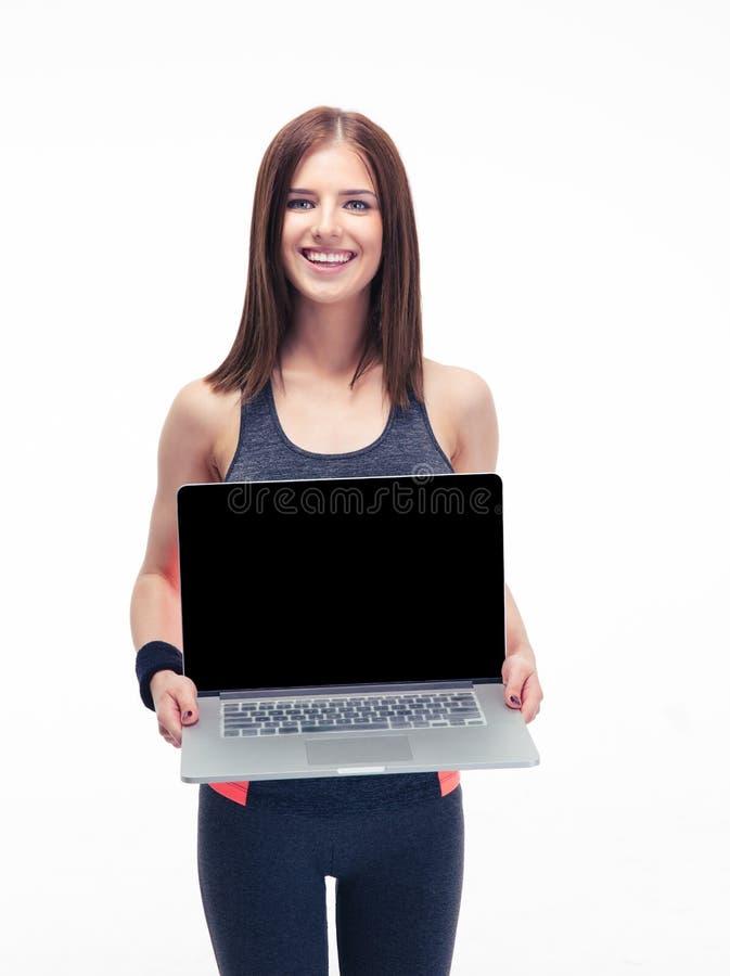 Donna felice di forma fisica che mostra lo schermo del computer portatile fotografie stock libere da diritti