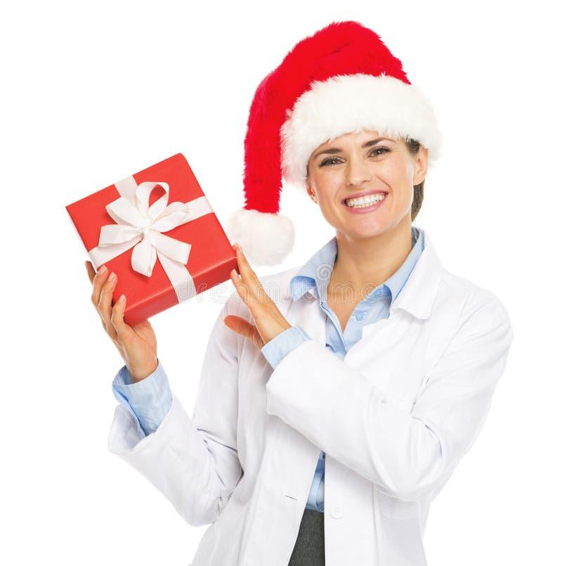 Donna felice di medico in cappello di Santa che mostra la scatola del regalo di Natale fotografia stock libera da diritti