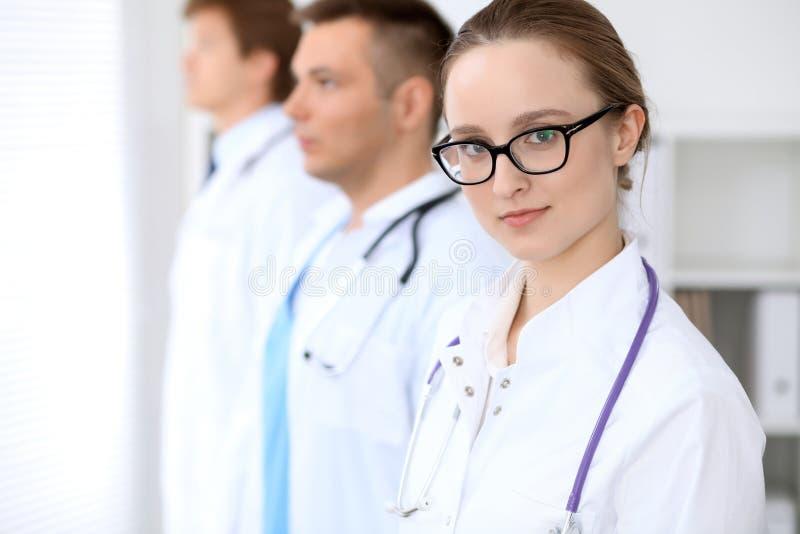 Donna felice di medico con il personale medico all'ospedale immagini stock libere da diritti