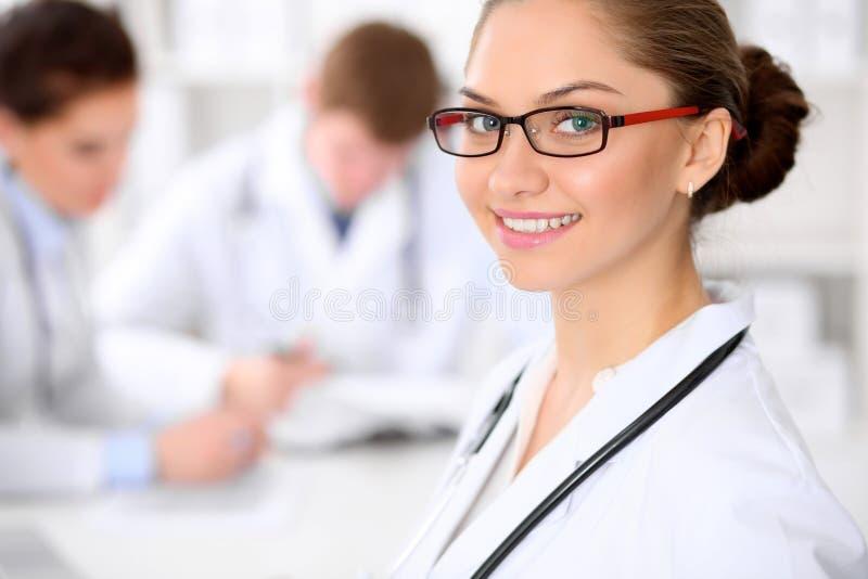 Donna felice di medico con il personale medico all'ospedale che si siede alla tavola fotografia stock libera da diritti
